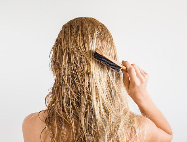 An image showing a woman combing her wet hair using a hair brush